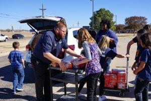 students help unload food donation by gene messer