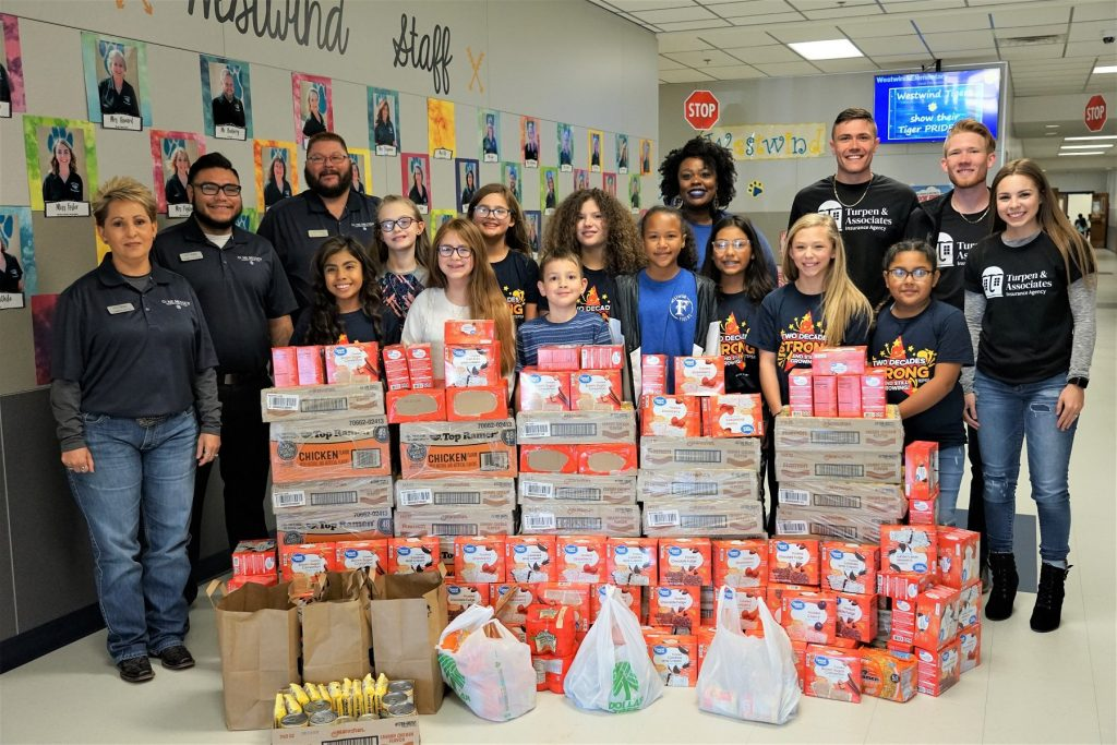 gene messer poses with westwind students after making food donation